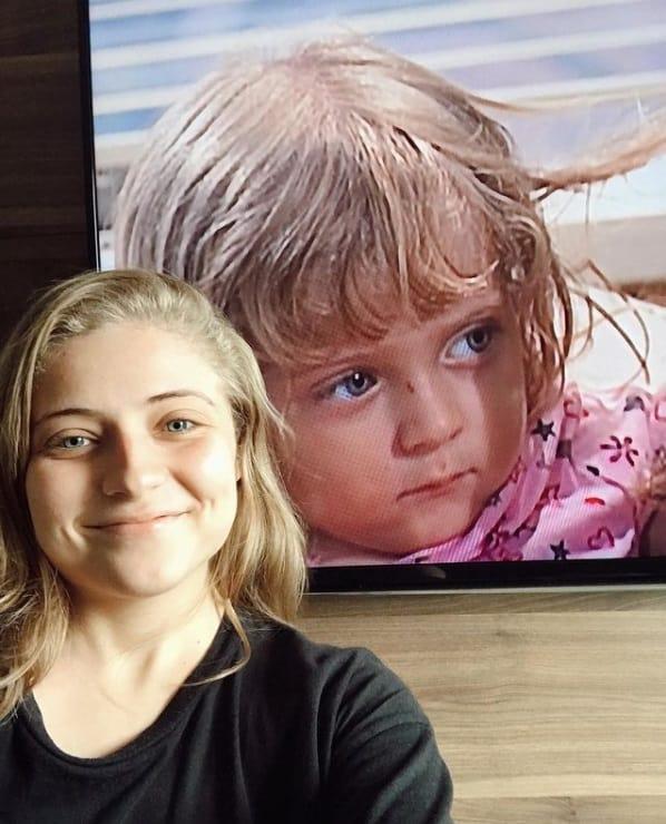 Júlia Maggessi diante de uma imagem sua em Laços de Família