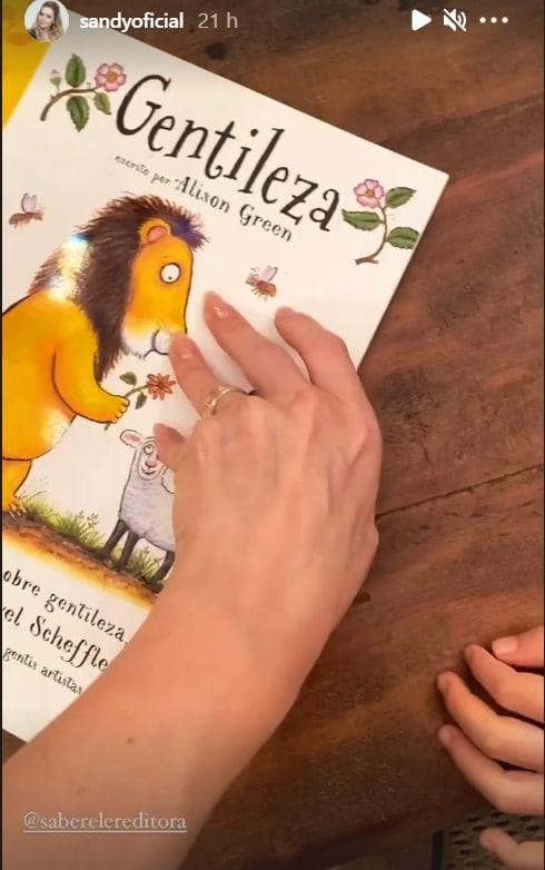 Sandy lendo um livro infantil com o filho