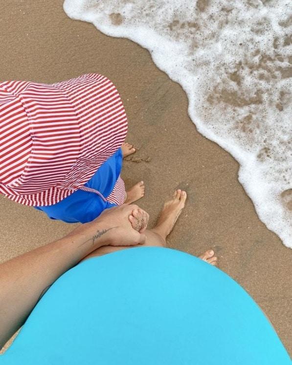 Monica Benini grávida e na praia com seu bebê com Junior Lima