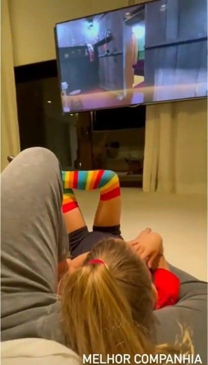 Angélica e Luciano Huck mostrando a filha na sua sala de TV gigante