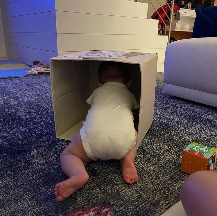 Bebê de Tiago Leifert brincando com caixa de papelão na sua casa
