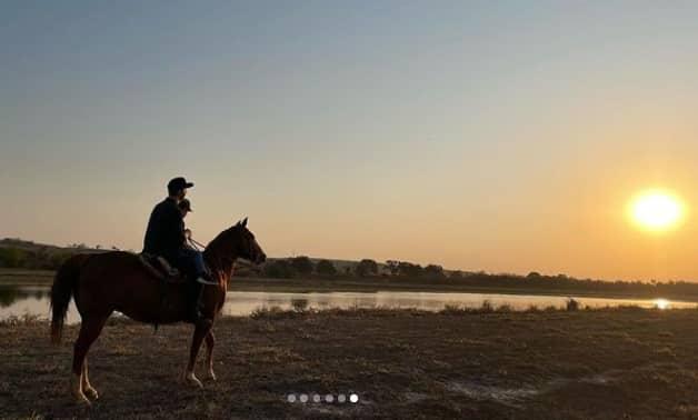 Sandy mostrando o filho passeando a cavalo