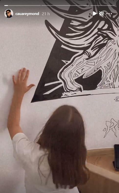 Cauã Reymond mostrando a filha realizando uma pintura