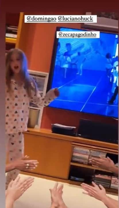 Angélica mostrando a filha na sua sala de televisão gigante
